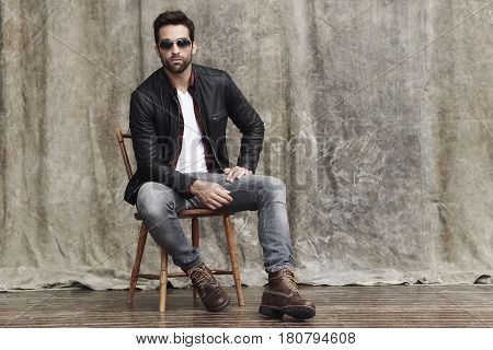 Posing guy in shades on chair in studio