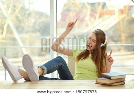 Beautiful young woman listening to music at home