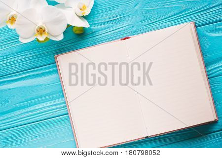 Open notebook with cup of coffee on blue wooden desk