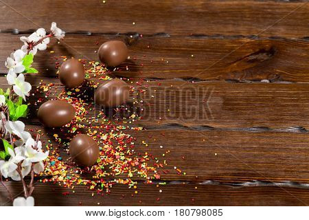 Beautiful Easter Composition With Chocolate Eggs, Colored Powder For Cakes On Old Brown Wooden Backg