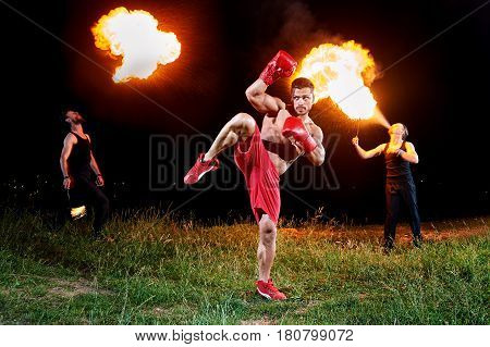 Professional kick boxer practicing outdoors at night fire eaters blowing fire from their mouths on the background creative extreme fiery artists performance champion winning training sports fitness.