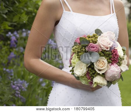 Midsection of young bride holding bouquet in formal garden
