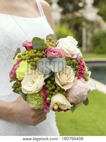 Midsection of young bride holding bouquet in garden
