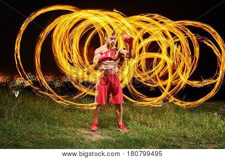 Shot of a young shirtless male fighter with strong fit and toned muscular body training outdoors at night fire and flames on the background copyspace burning fiery flame hot masculinity courage fight.
