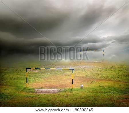 Football field, football goal, deflated ball and cloudy sky