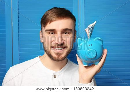 Happy young man holding piggy bank with money on color folding screen background