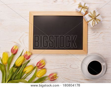 Black board with blank space for text, bouquet of tulips, cup of coffee  and gift boxes on a wooden background. Top view with copy space. Greeting card. Advertising.