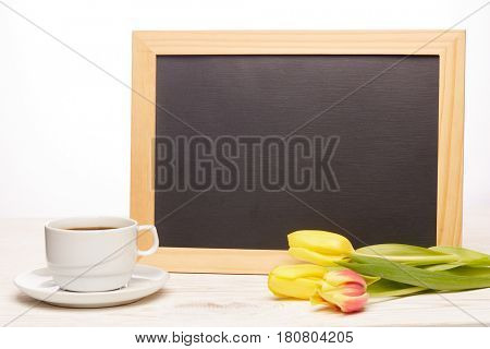 Black board with blank space for text, tulips and cup of coffee on a wooden table on a light wooden background. Copy space for adding your content. Menu. Advertising