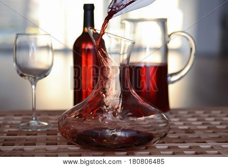 Pouring red wine into decanter on blurred background