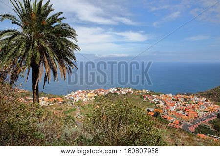 AGULO, LA GOMERA, SPAIN: General view of the village from a mountain trail with Teide volcano (Tenerife island) in the background