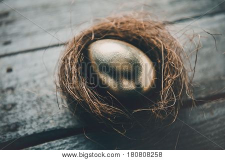 Close-up View Of Golden Easter Egg In Nest On Wooden Table, Happy Easter Concept