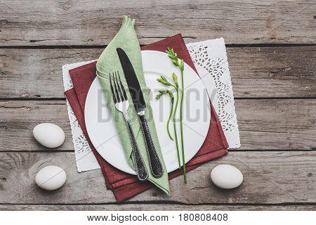 Top View Of Easter Table Setting With Cutlery, Spring Plant And Easter Eggs On Wooden Table, Happy E