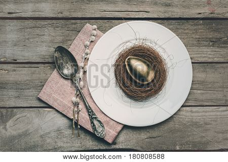 Top View Of Golden Easter Egg In Nest On White Plate, Napkin, Catkins And Vintage Spoon On Wooden Ta