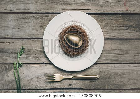 Top View Of Golden Easter Egg On White Plate With Fork And Green Plant On Wooden Table, Happy Easter