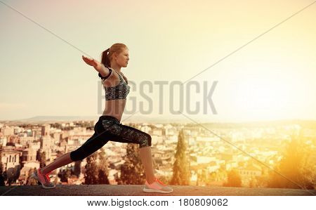 Concentrated fitness woman practicing yoga on mountain peak at sunset. Concept of healthy lifestyle and tranquility.