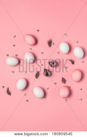 Top View Of Pink And White Eggs With Bunnies, Catkins And Feathers On Pink. Happy Easter Concept