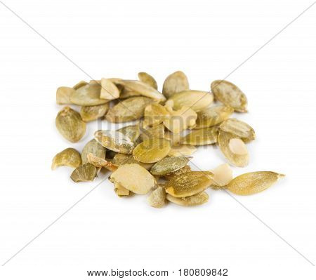 Pile of peeled skinless pumpkin seeds close-up isolated on white background. Lots of healthy vegan and vegetarian food, rich of energy low fat nutrition