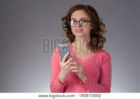 beautiful young woman spectacled  in a pink shirt expresses emotions with smartphone pushes his finger and smiling on a gray background