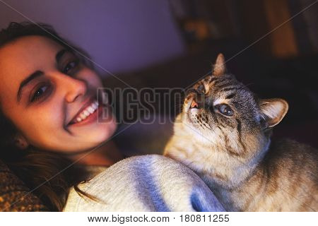 young woman with striped cat at evening sits on sofa in dark room with the table lamp. Woman smiling and stroking a cat. Tenderness and care for your pet. pets, evening, comfort, rest and people concept