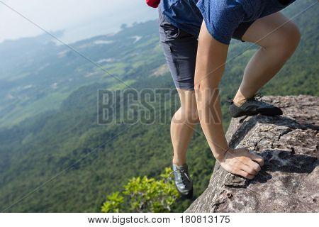 success young woman rock climber on mountain peak
