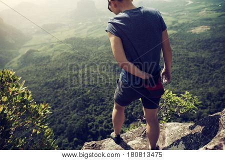 success young woman rock climber on mountain peak