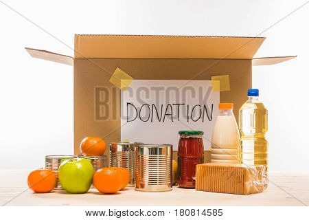 Different Food With Cardboard Box And Donation Sign On Wooden Table On White, Donation Concept