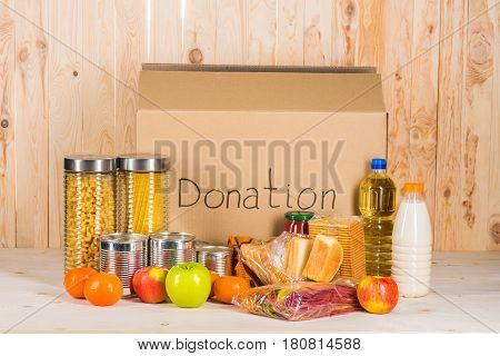 Different Food With Cardboard Box And Donation Sign On Wooden Table, Donation Concept