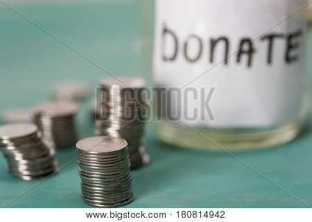 Close-up View Of Stacked Coins And Glass Jar For Donate, Donation Concept