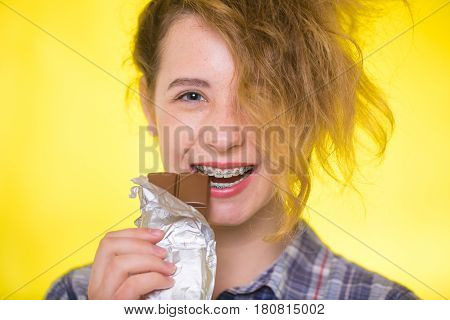 Young girl in a plaid shirt on yellow background showing her dental braces and bites the chocolate