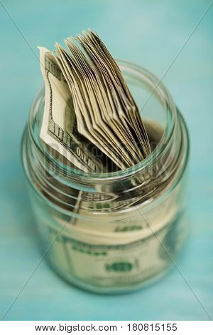 Close-up high angle view of dollar banknotes in glass jar donation concept