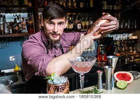 Smiling and cheerful barman prepares drinks in the club at the bar