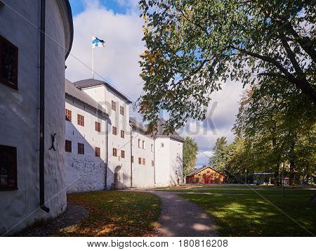 Turku Castle In Bright Sunshine In Finland With The Finnish Flag On A Sunny Summer Day
