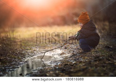 Little boy playing in puddle at springtime. Happy childhood
