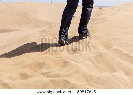 Woman goes in the dunes to the beach
