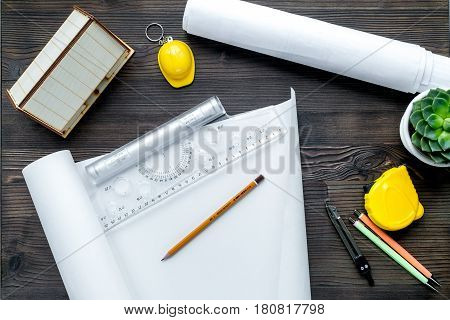 architect working desk with project and ruler on wooden background top view