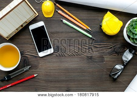 architect working desk with mobile, cup of tea, project and pens on wooden background top view mock-up