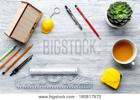 architect office with tools, cup and flower in profession concept on light wooden desk background top view mock-up