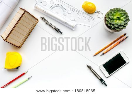Architects workplace with constructor tools with miniature and mobile on white table background top view mock up