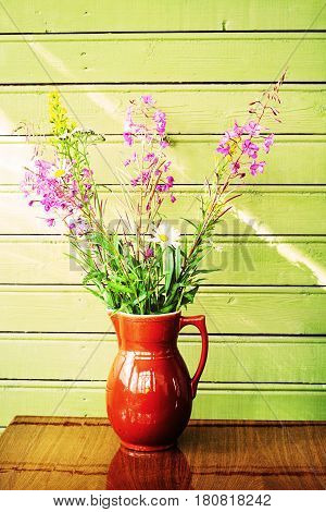 Ceramic pitcher with wildflowers on the background of a wooden wall