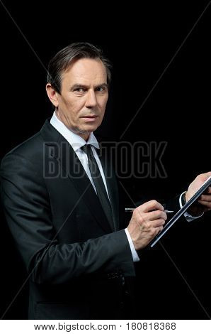 Serious Mature Businessman With Clipboard Signing Contract And Looking At Camera