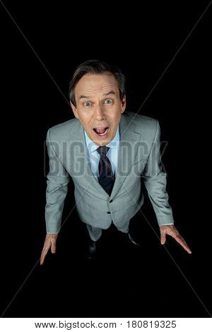 overhead view of middle aged shocked businessman in suit yelling on black