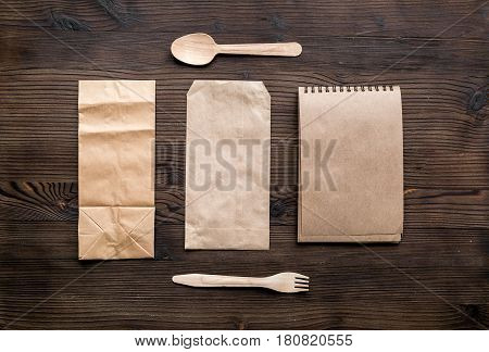 paper bags and flatware in delivery concept on wooden table background top view