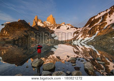 man standing near lake under towers of Fitz Roy mountain and at red sunrise