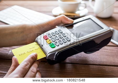 Payment in cafe for business lunch concept with credit card and terminal on wooden desk background