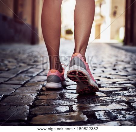 Female tourist traveling along Spanish street. Close-up of woman hiker feet walking on paving stone on summer day.