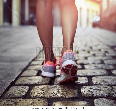 Young sporty woman sprinting along the street. Close-up of runner sneakers on asphalt road on sunset.