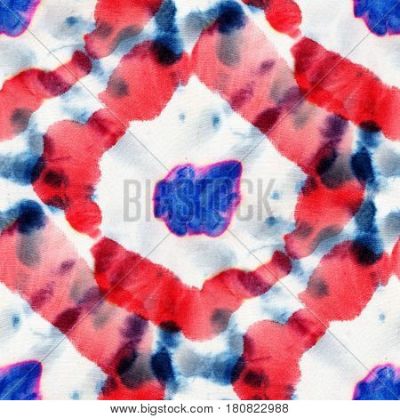 Seamless tie-dye pattern of red and blue color on white silk. Hand painting fabrics - nodular batik. Shibori dyeing.