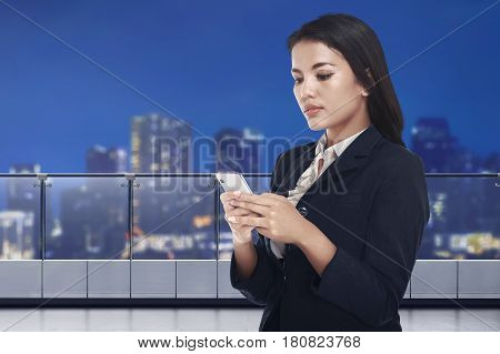 Young Asian Business Woman Messaging On Mobile Phone