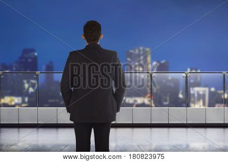 Back View Of Asian Businessman Looking At The City Through Window