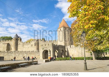 Carcassonne, France - October 20, 2016; Tourists arriving at stone wall and turrets at drawbridge entrance to medieval castle or fort know as La Cite de Carcassonne France